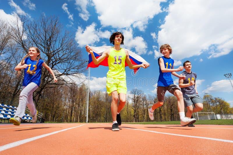 Gelukkige Russische sprinters die op het stadion lopen stock afbeeldingen