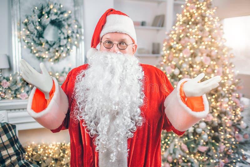 Gelukkige Santa Claus bevindt zich en kijkt op camea Hij stelt opzij met handen van lichaam Mensenglimlachen Er is feestelijke Ke stock foto