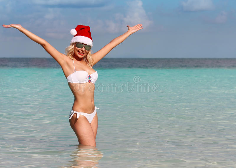 Gelukkige Santa Girl op Tropisch Strand. Mooie blonde jonge vrouw stock afbeelding