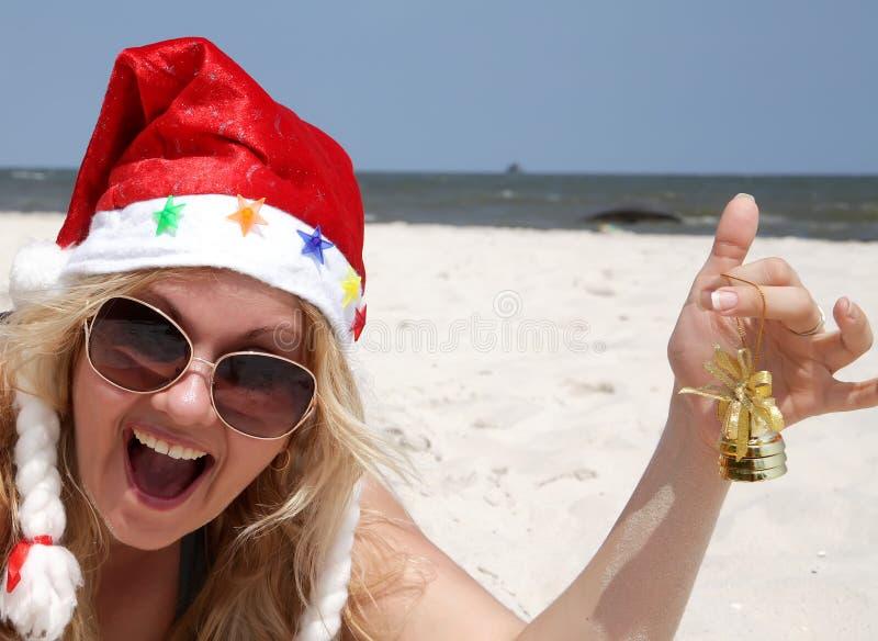 Gelukkige santavrouw met klok op het strand stock afbeeldingen