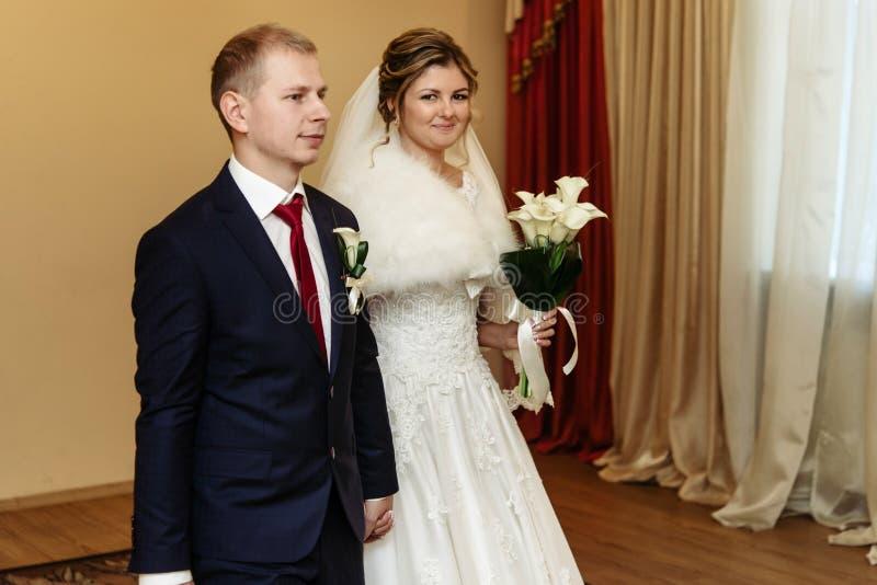 Gelukkige schitterende bruid en modieuze bruidegom die trouwringen ruilen stock foto