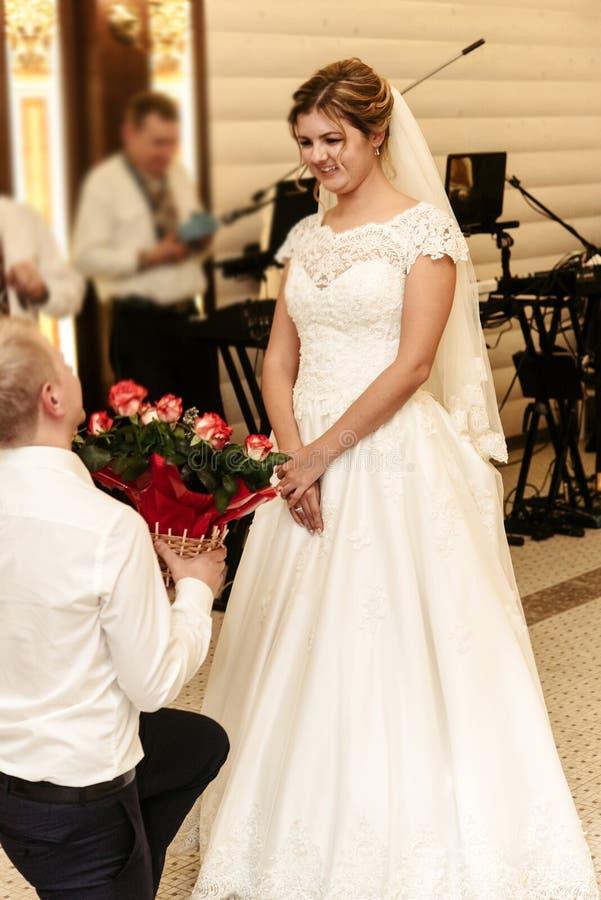 Gelukkige schitterende bruid en modieuze bruidegom met verrassingsboeket van royalty-vrije stock foto
