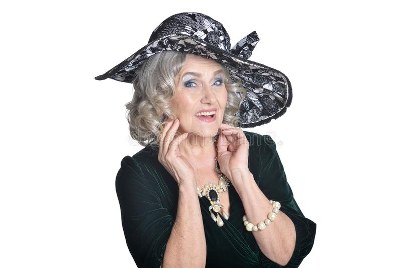 Gelukkige schitterende rijpe vrouw in hoed stellen ge?soleerd op witte achtergrond stock afbeeldingen