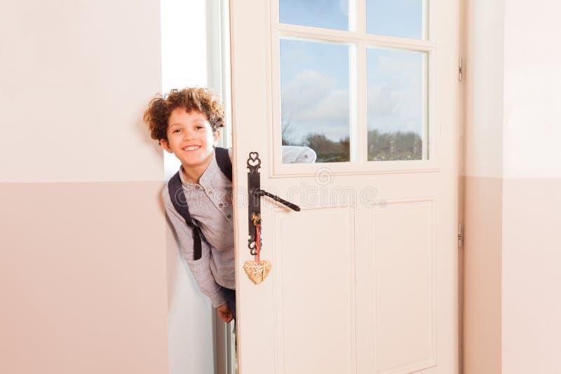 Gelukkige schooljongen die door de deuropening kijken stock foto's