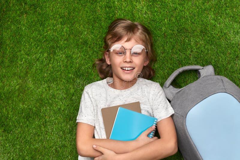 Gelukkige schooljongen die op groen gras liggen stock afbeelding