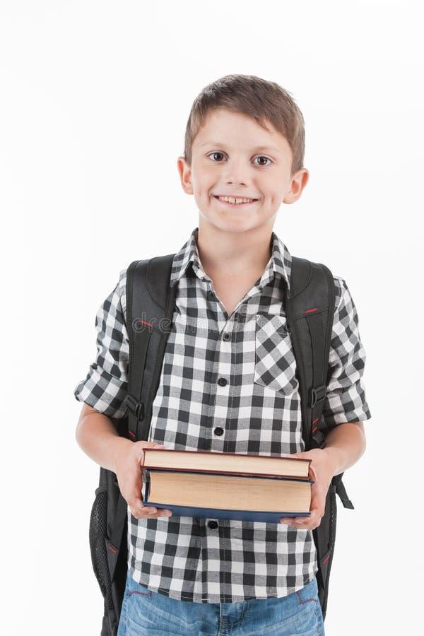 Gelukkige schooljongen die rugzak dragen en boeken houden stock foto