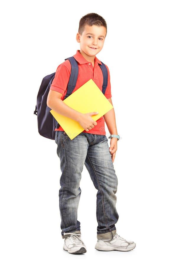 Gelukkige schooljongen met de boeken van de rugzakholding stock foto