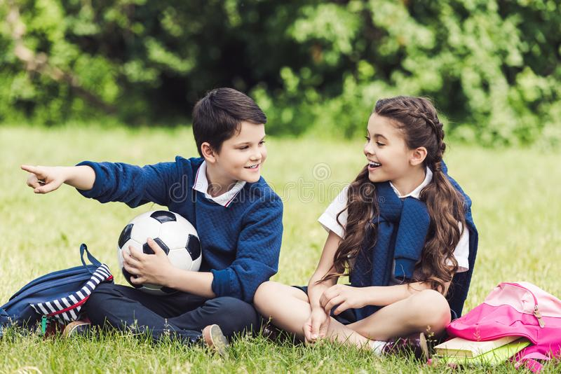 gelukkige schoolkinderen die op gras in park met rugzakken en voetbalbal zitten stock afbeelding