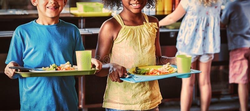 Gelukkige schoolkinderen die voedseldienblad in kantine houden stock afbeeldingen