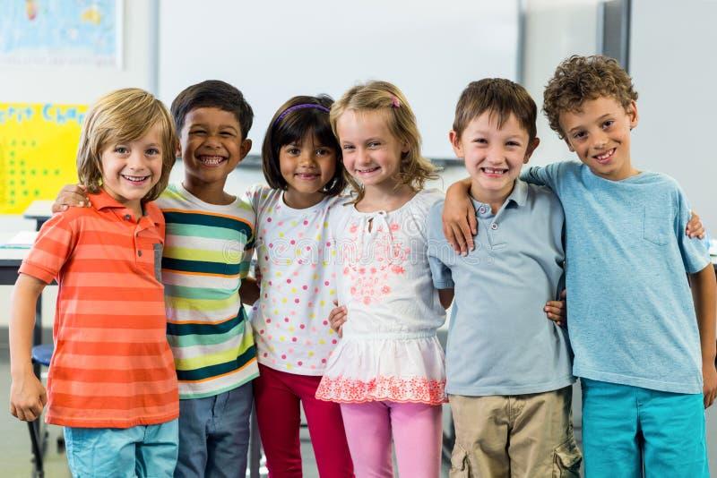 Gelukkige schoolkinderen die zich in klaslokaal bevinden royalty-vrije stock fotografie