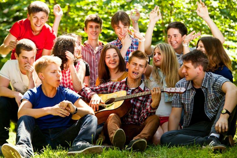 Gelukkige schoolvrienden die door gitaar zingen stock foto
