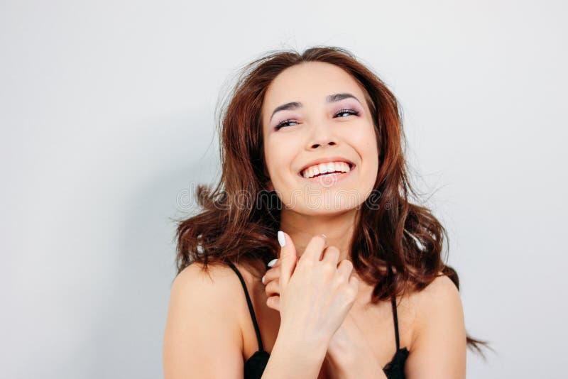Gelukkige sensuele glimlachende meisjes Aziatische jonge vrouw met donker lang krullend haar in zwart ondergoed op witte achtergr stock fotografie