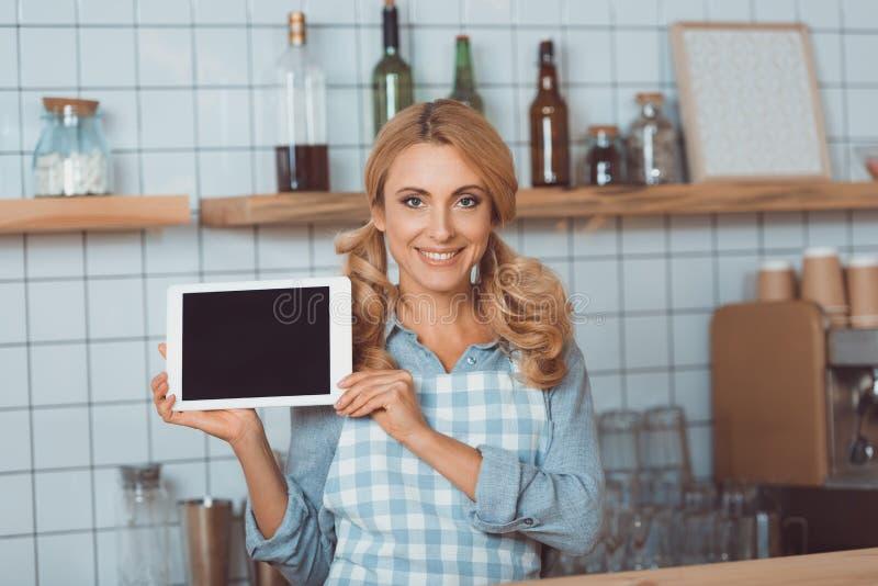 gelukkige serveerster die in schort digitale tablet met het lege scherm en het glimlachen houden royalty-vrije stock foto's