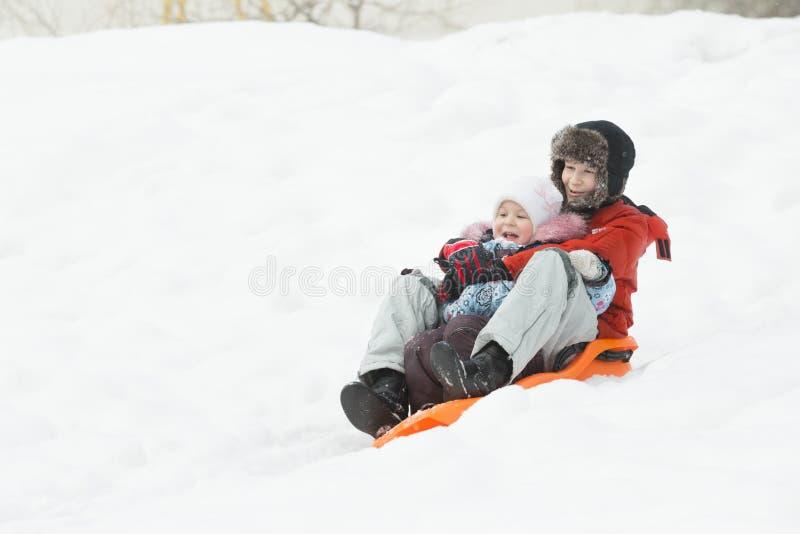Gelukkige siblings die bergaf pret op schuif van de de winter de oranje plastic sneeuw hebben royalty-vrije stock afbeeldingen
