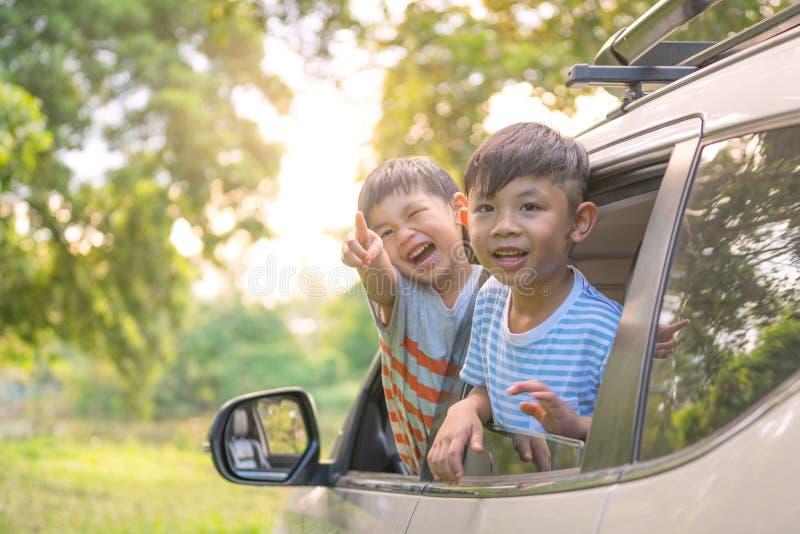 Gelukkige siblings die handenreis golven door auto tegen blauwe hemel De reisconcept van de de zomerweg royalty-vrije stock afbeelding