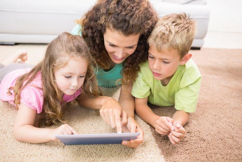 Gelukkige siblings die op de deken liggen die tablet met hun moeder gebruiken stock afbeeldingen