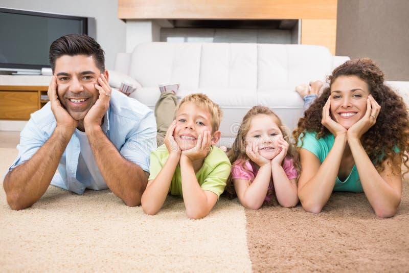 Gelukkige siblings die op deken het stellen met hun ouders liggen royalty-vrije stock fotografie