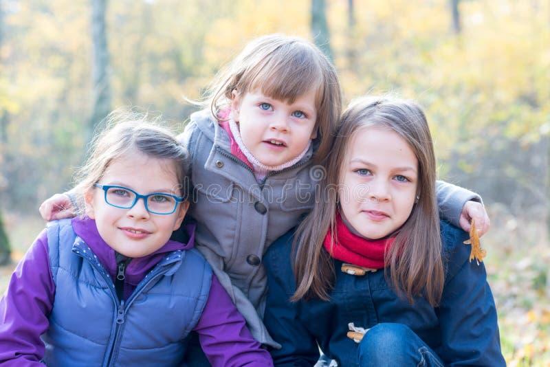 Gelukkige siblings - Drie zusters in het herfst bos glimlachen stock afbeelding