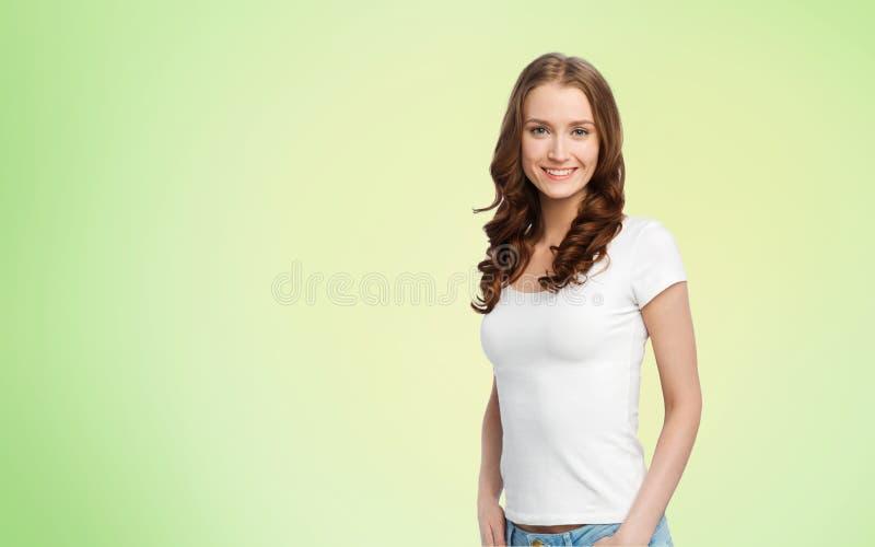 Gelukkige slanke vrouw in witte t-shirt over groene kalk stock afbeelding