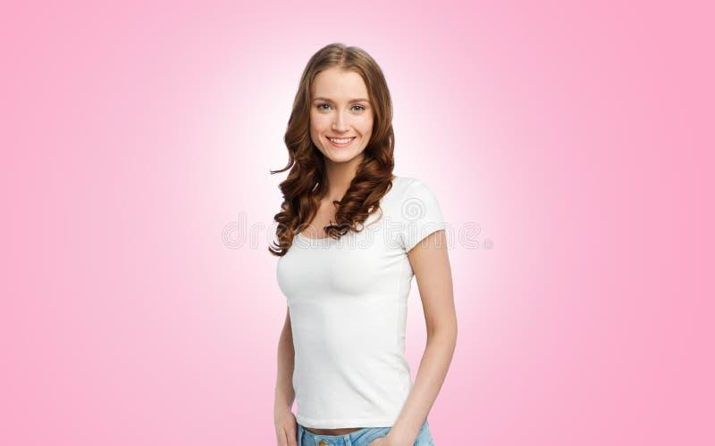 Gelukkige slanke vrouw in witte t-shirt over roze royalty-vrije stock fotografie