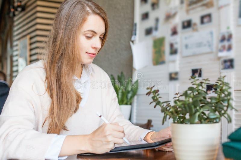 Gelukkige slimme onderneemster in vrijetijdskledingszitting met laptop gadget die in bureauplaats werken stock afbeeldingen