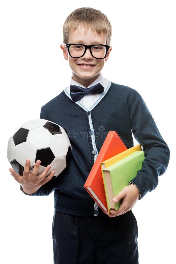 Gelukkige slimme schooljongen met een handboek van de voetbalbal op witte bac stock afbeelding