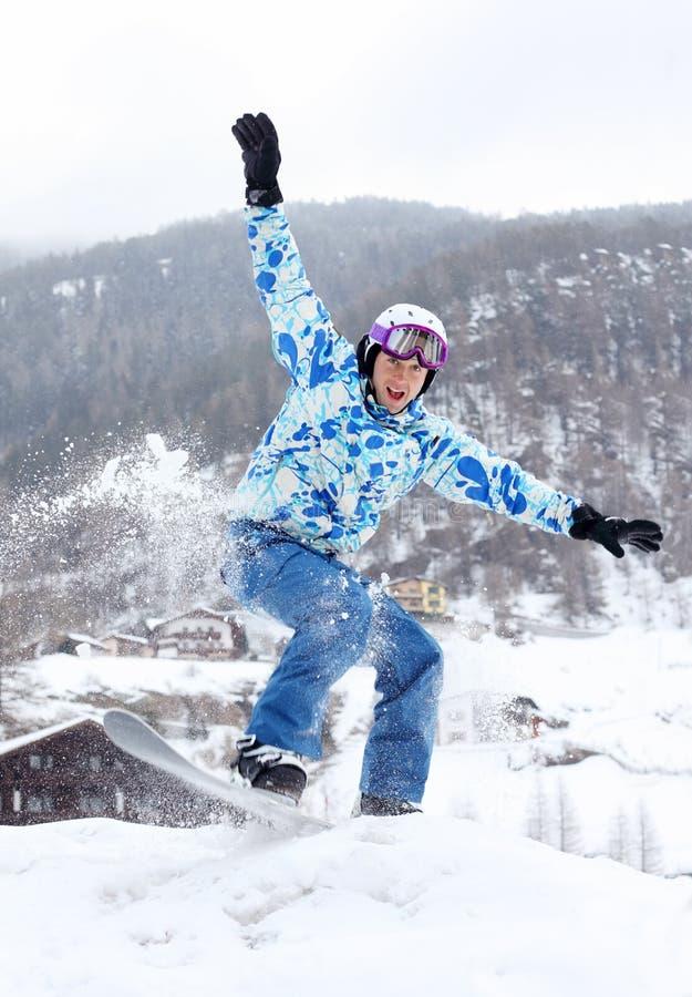Gelukkige snowboardersprongen op snowboard en srceams stock foto's