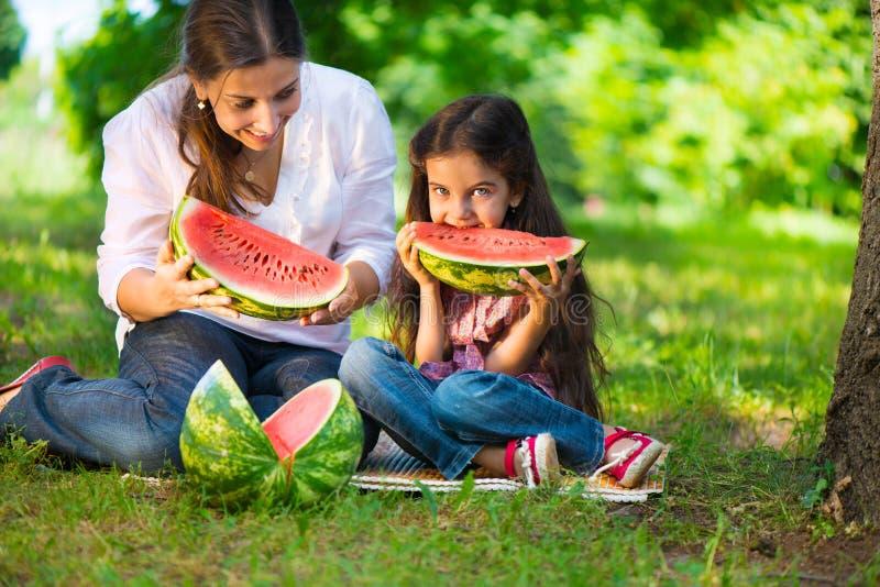 Gelukkige Spaanse familie die watermeloen eten royalty-vrije stock afbeelding
