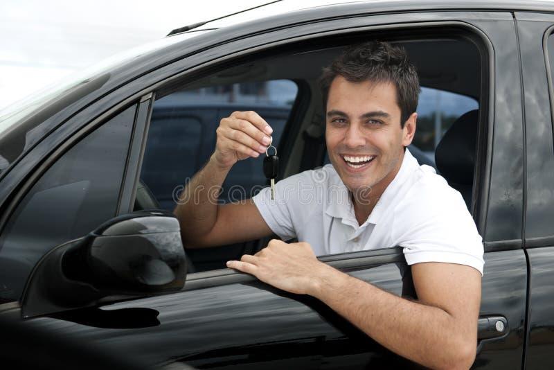 Gelukkige Spaanse mens in zijn nieuwe auto stock afbeelding