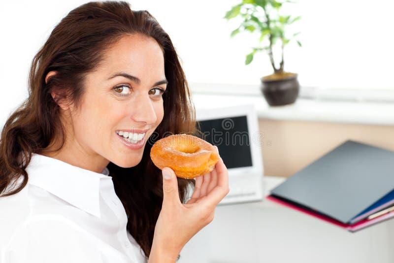 Gelukkige Spaanse onderneemster die een doughnut eet royalty-vrije stock afbeelding