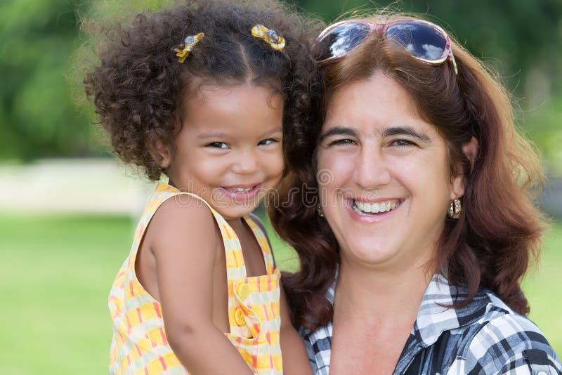 Gelukkige Spaanse vrouw die een klein meisje vervoeren royalty-vrije stock afbeelding