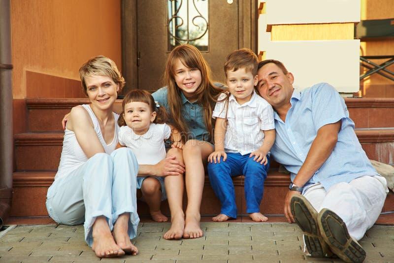 Gelukkige speelse familie op de portiek van zijn huis Ouders met kinderen Mamma, papa en jonge geitjes stock afbeelding