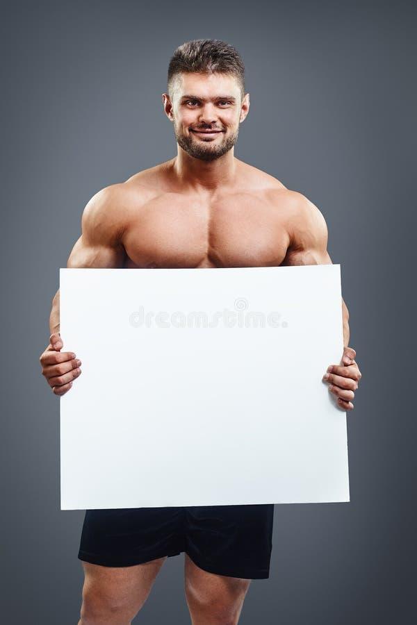 Gelukkige spier shirtless mens die en aanplakbiljet tonen tonen royalty-vrije stock afbeeldingen