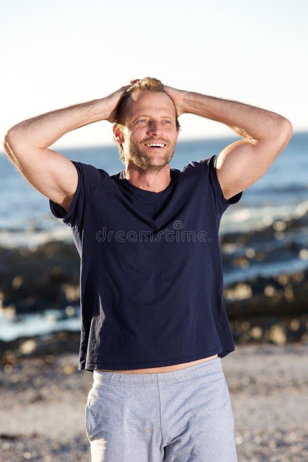 Gelukkige sportenmens die buiten met handen achter hoofd glimlachen stock fotografie