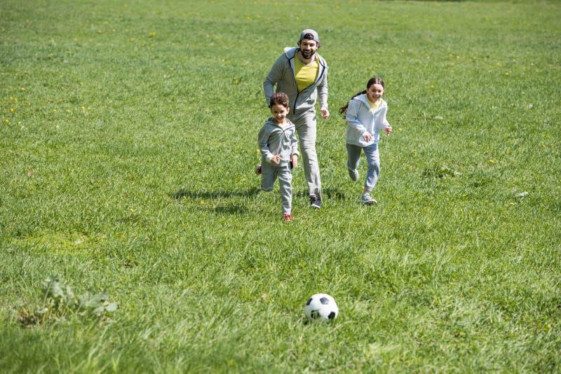 gelukkige sportieve familie speelvoetbal op grasrijk stock foto