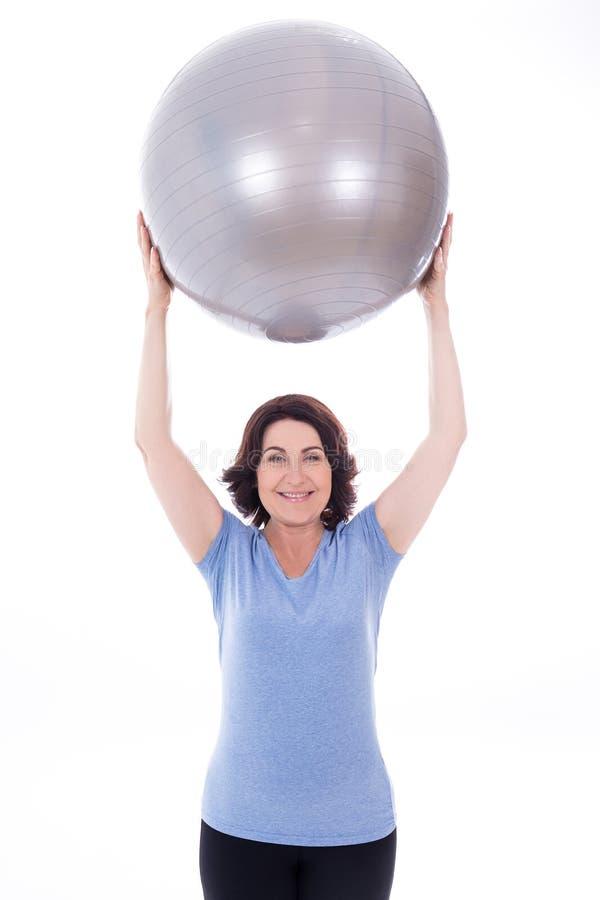 Gelukkige sportieve rijpe die vrouw met geschiktheidsbal op wit wordt geïsoleerd stock afbeelding
