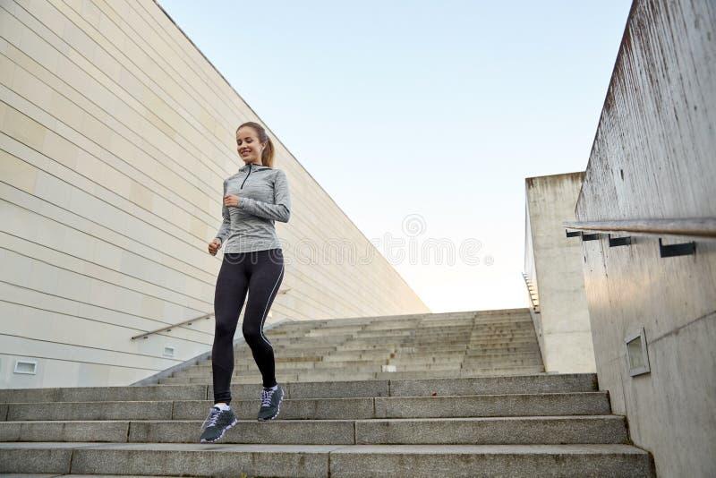Gelukkige sportieve vrouw die beneden in stad lopen royalty-vrije stock fotografie