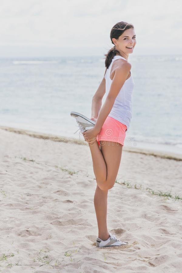 Gelukkige sportieve vrouw die benen doen die zich vóór jogging uitrekken royalty-vrije stock afbeelding