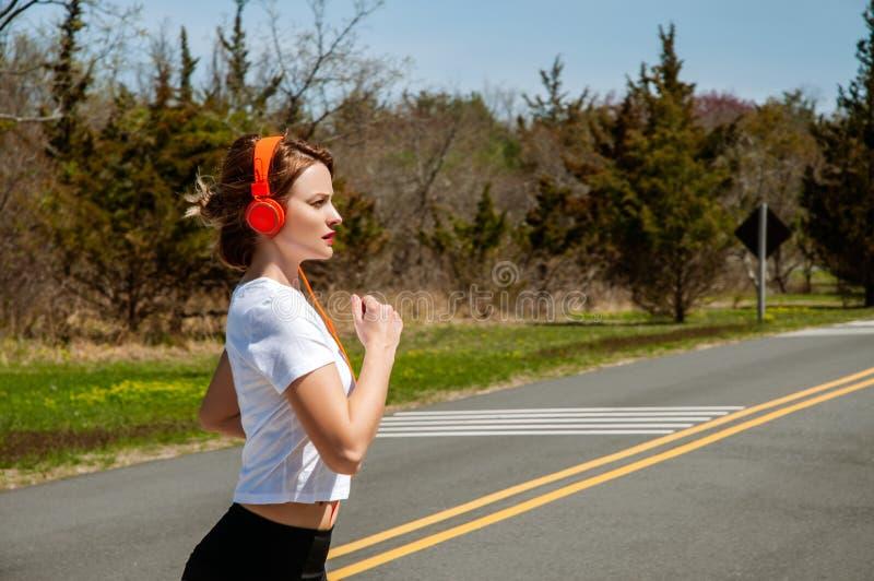 Gelukkige sportieve vrouw die en aan muziek lopen luisteren royalty-vrije stock foto