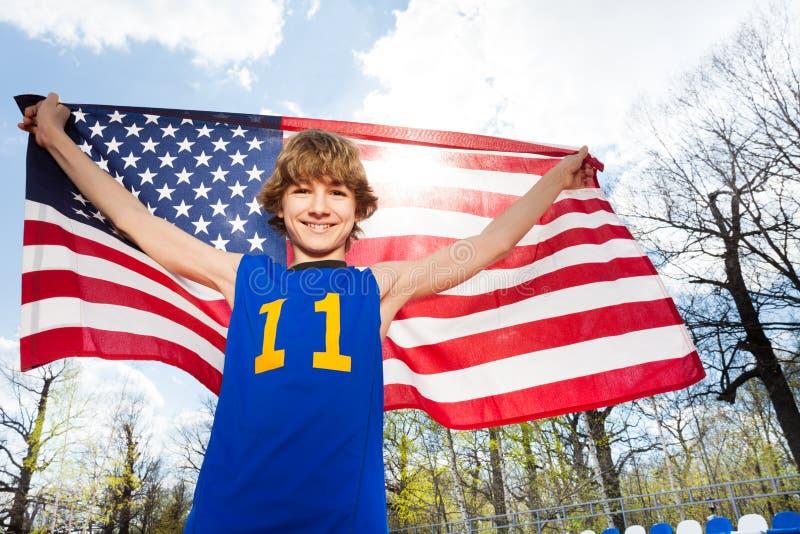 Gelukkige sportman die Amerikaanse vlag op stadion houden royalty-vrije stock fotografie