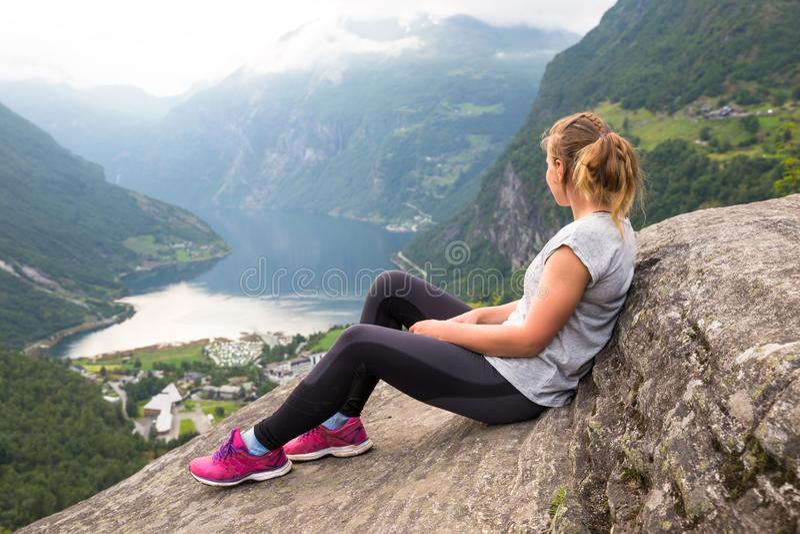Gelukkige sportvrouw die in Geirangerfjord wandelen noorwegen royalty-vrije stock afbeelding