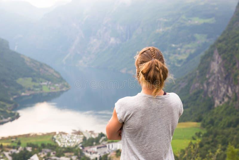 Gelukkige sportvrouw die in Geirangerfjord wandelen noorwegen stock foto