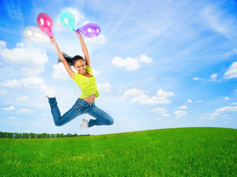Gelukkige springende jonge vrouw met ballons openlucht stock foto's