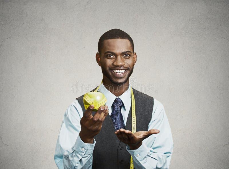 Gelukkige stafmedewerker die op gezonde voeding adviseren, die groene appel houden stock afbeelding