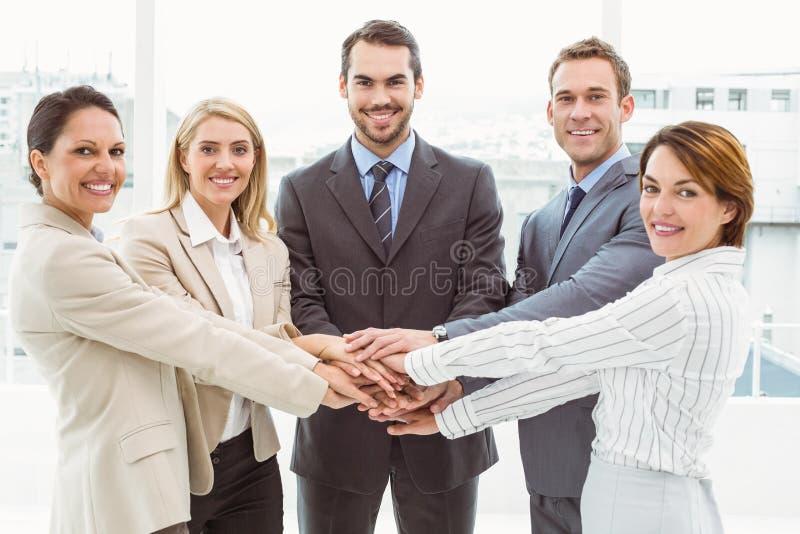 Gelukkige stafmedewerkers die handen samen in bureau houden stock fotografie