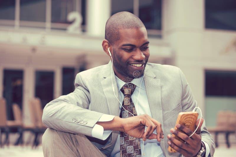 Gelukkige stedelijke professionele mens die slimme telefoon met behulp van die aan muziek luisteren stock afbeelding