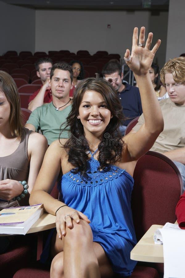 Gelukkige Student Answering In Class stock afbeelding