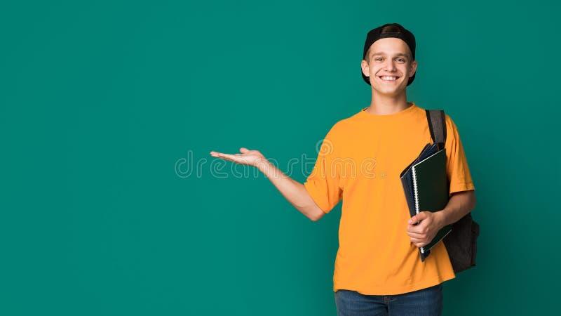 Gelukkige student die met boeken iets op palm houden royalty-vrije stock foto's