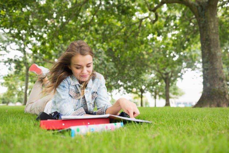 Gelukkige student die op gras het bestuderen liggen stock fotografie