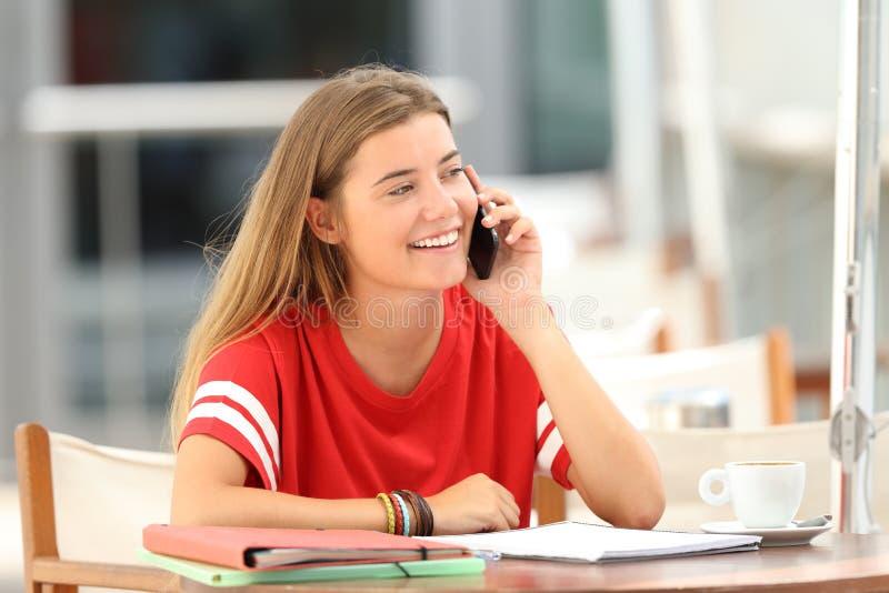 Gelukkige student die op telefoon in een bar spreken royalty-vrije stock foto